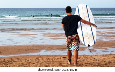Young man walking towards the ocean carrying a surfboard and wearing cool boardshorts