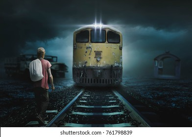 Young man walks along the railroad tracks in the night alone.