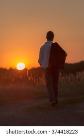 A young man walks lonely in a sundown