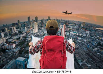 Young man wanderer holding a map and searching direction on location map and look to the city top view with searching direction in a map while traveling abroad. Tourist searching location concept