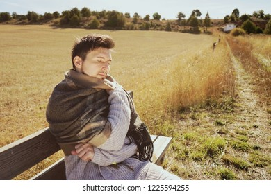 A young man with a warm scarf enjoying in calm the morning autumn sun in a yellow field with the backlight from the blue sky