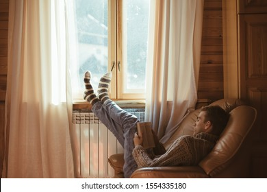Young man in warm sweater reading book while relaxing on armchair by the window and electric radiator inside cozy log cabin