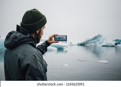 Young man in warm winter clothing stands on beach in iceland or greenland and makes photo on smartphone of icebergs and glaciers floating in water, slowly melting and raising ocean level