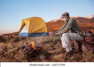 Young Man Warming Up by Campfire