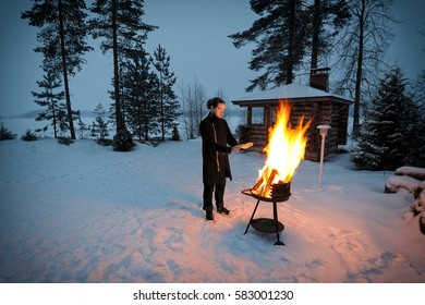 Young man warms himself by the fire on a winter evening