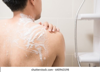 A young man wash his body.