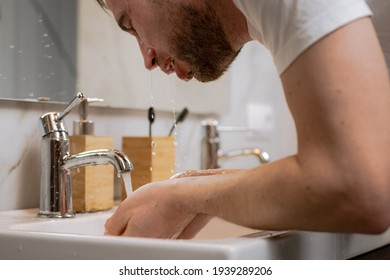 A young man washes his face in the bathroom with a splash of water. Hygiene and cleanliness of the body. Morning treatments for men.