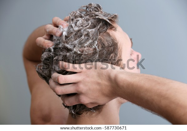 Young man washing hair on color background