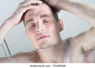 Young man washing head with shampoo