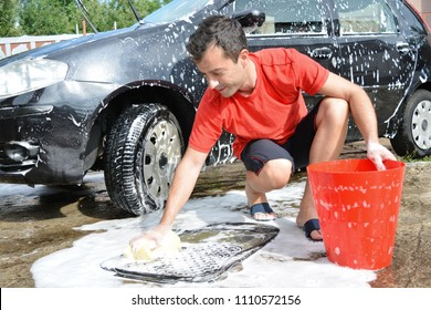 Young man washing his car in summer hot day. Smiling and relaxing while cleaning