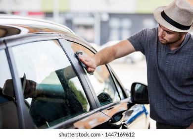 Young man washing his car in car wash