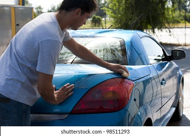 Young man washing his car with sponge