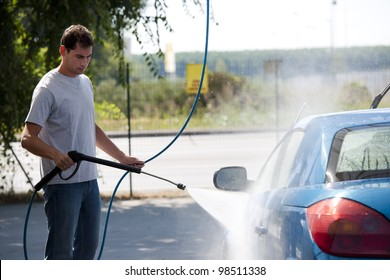 Young man washing his car with compression water
