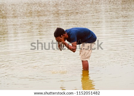 Young man washing his face using lakes water isolated unique photo