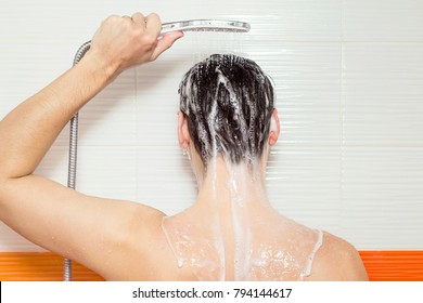 young man washing his hair and back, taking a shower with foam on his body, holds in his hand a shower in bathroom, he use shampoo, attractive young guy is cleaning his body, health care concept
