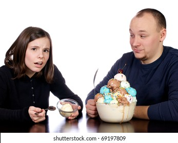 Young man watches his wife complain at her small one scoop bowl of vanilla ice cream as he sits in front of his giant bowl of multi-flavored scoops of ice cream.