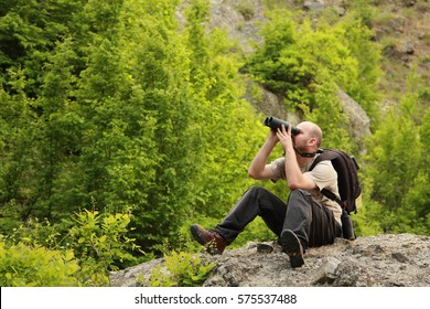 A young man watching birds trought binoculars in the mountain early morning
