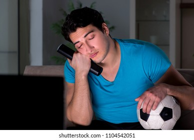 Young man watching football late at night