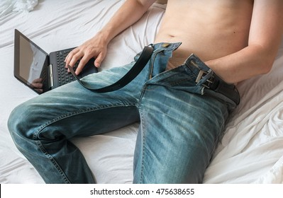 Young man is watching pornography on laptop and masturbating.