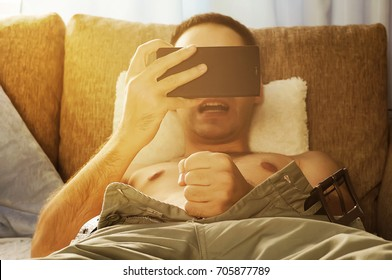 young man watching pornography on a mobile screen and masturbating.