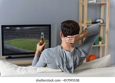 Young man watching television at home