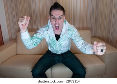 Young man watching television and yelling