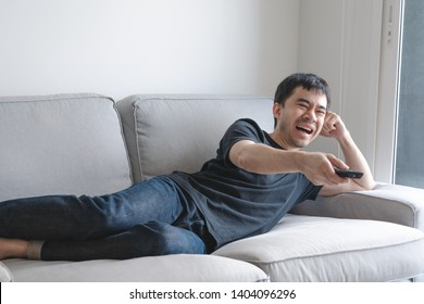 Young man watching tv and laughing while using remote control. Sitting on sofa with high resolution files
