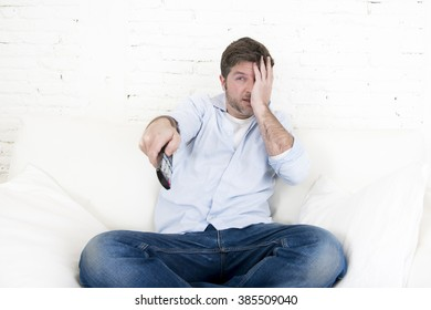 young man watching tv sitting at home living room sofa holding remote control looking scared and in fear covering his eyes with his hand enjoying television horror movie program