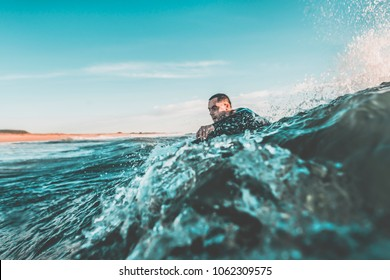 Young man with the water up to the neck trying to catch a wave with his bodyboard among the rough waters of the sea. Extreme water sports and outdoor active lifestyle. Vintage filter with soft style