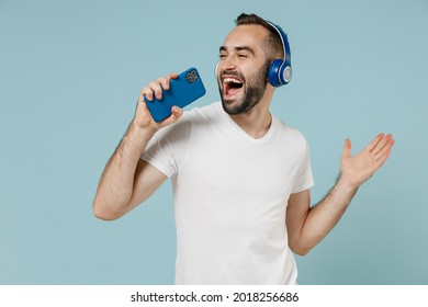 Young man wear blank print design white t-shirt headphones listen to music sing song record voice by mobie cell phone dictaphone isolated on plain pastel light blue color background studio portrait.