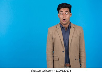 Young man wearing beige blazer looking aside open his mouth shocked on blue background.