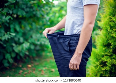 Young man wearing big loose jeans outdoor - weight loss concept