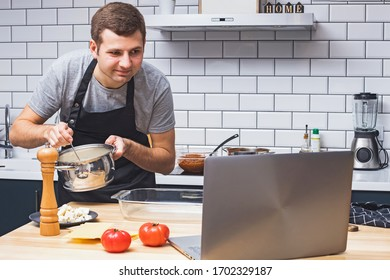 Young man wearing black apron in the modern kitchen looking for recipes on his laptop. Cooking in home, online recipe, remote cooking classes