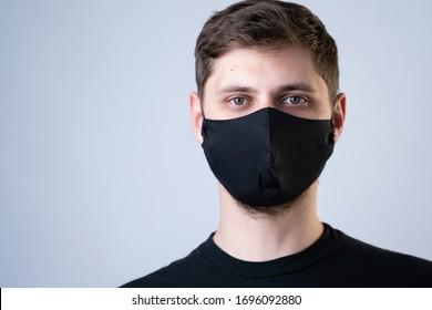 Young man wearing black face mask. Pandemic coronavirus covid-19 quarantine period concept.