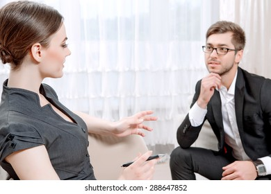Young man wearing a black suit sitting on a couch looking at his doctor and listening, psychologist with clipboard talking to him and making notes during therapy session, selective focus
