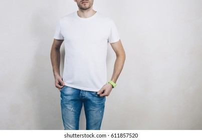 Young man wearing blank tshirt and blue jeans on the white background. Front side.