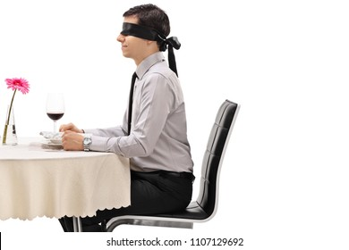 Young man wearing a blindfold seated at a restaurant table isolated on white background