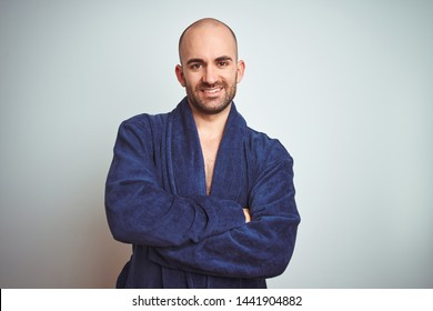 Young man wearing blue bathrobe, relaxed lifestyle over isolated background happy face smiling with crossed arms looking at the camera. Positive person.