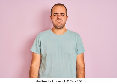 Young man wearing blue casual t-shirt standing over isolated pink background puffing cheeks with funny face. Mouth inflated with air, crazy expression.