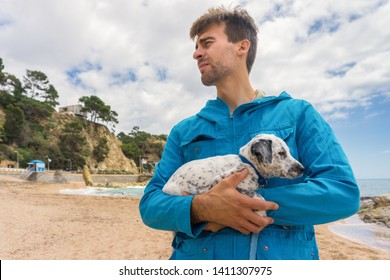 Young man wearing blue jacket holding his adopted mixed Dalmatian puppy in scenic place with blue sky, beach, and sea on background. Pets adoption concept. Costa Brava. Spain.