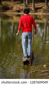Young man wearing blue jeans standing on a dead tree parts in the water