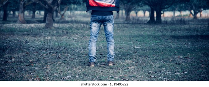 Young man wearing blue jeans standing around a park unique photo