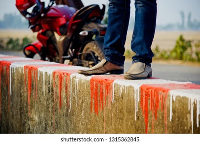 A young man wearing blue jeans standing on a concrete surface photo