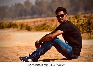 Young man wearing blue jeans and sunglass sitting in a place