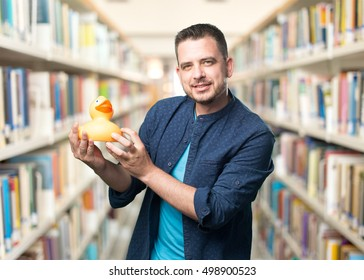 Young man wearing a blue outfit. Holding a toy duck.