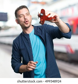 Young man wearing a blue outfit. Playing with a plane. Over train station background.