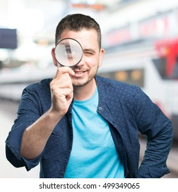 Young man wearing a blue outfit. Using a magnifying glass. Smiling. Over train station background.