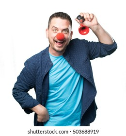 Young man wearing a blue outfit. Wearing a clown nose. Playing with red horn.