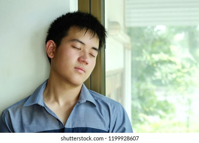 Young man wearing blue shirt is resting and sitting , close his eyes, feeling asleep at daytime.