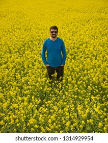 Young man wearing blue t shirt standing in a mustard crops field